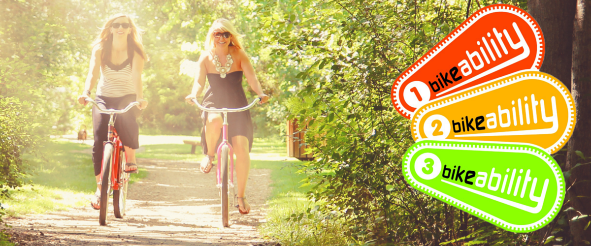Two women cycling through a park