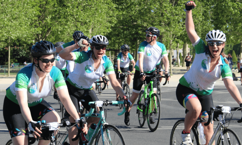 Charity riders cycling together arriving in Paris after cycling from Bristol
