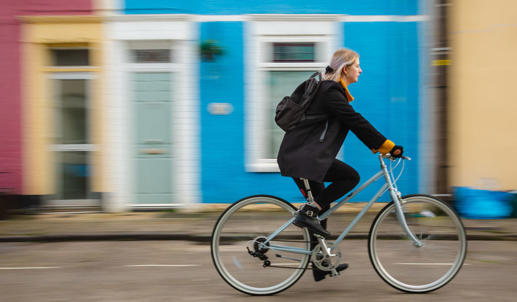 Young women cycling in colourful street