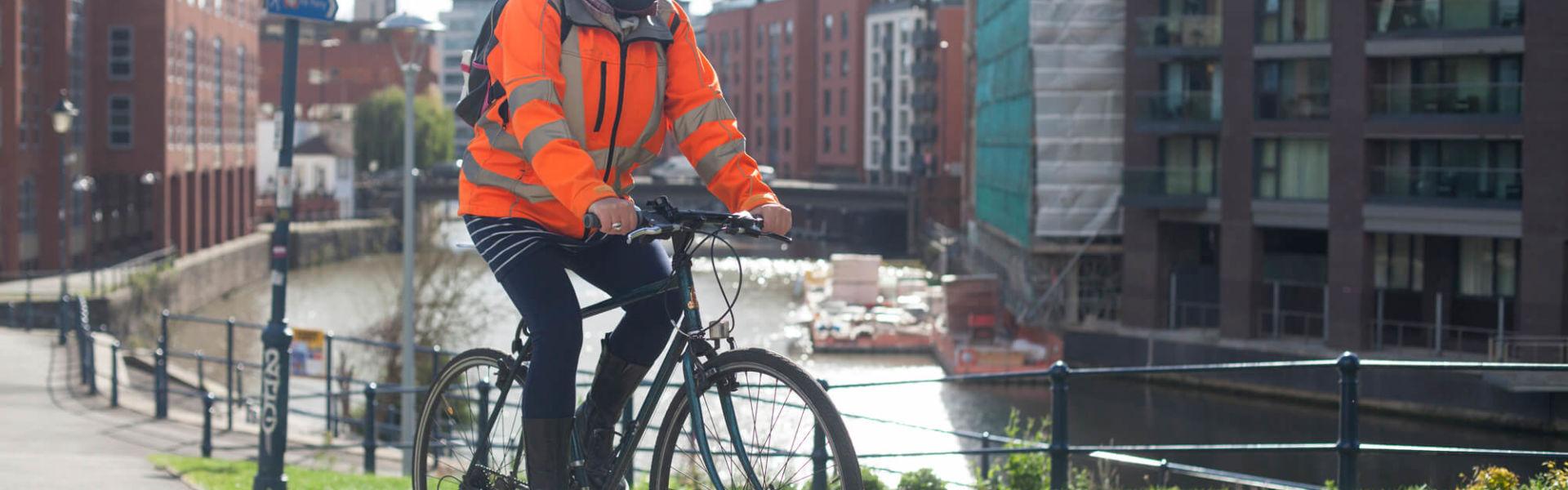 Women wearing hiviz cycling to work over a bridge