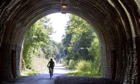 Cyclist riding through a tunnel along the Bristol to bath railway path