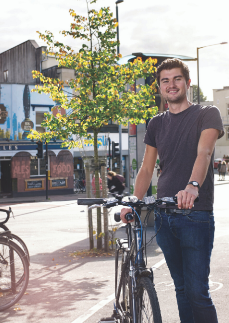 Young man standing with his bike on Gloucester Road Bristol