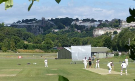 Scenic photo of people playing cricket with view of Clifton Suspension Bridge