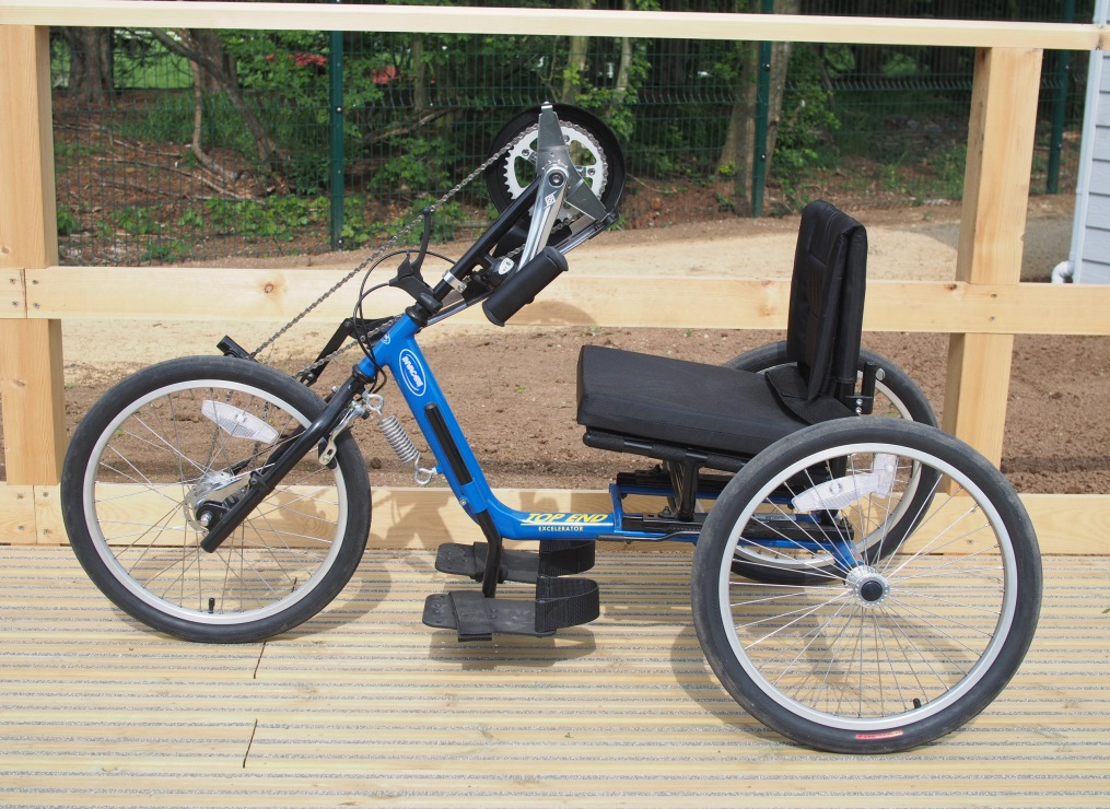 A blue adult size handcycle on a wooden platform