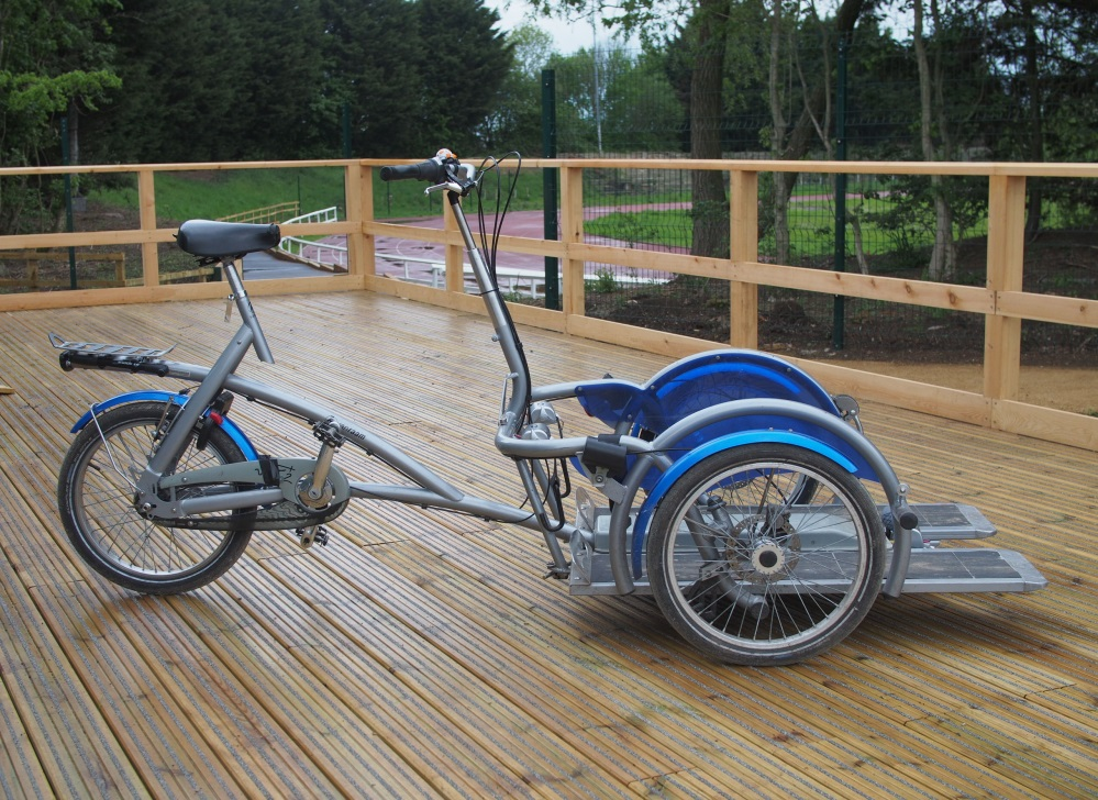 A silver adult size platform cycle on a wooden platform