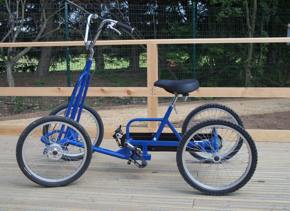 A blue adult size quadracycle on a wooden platform