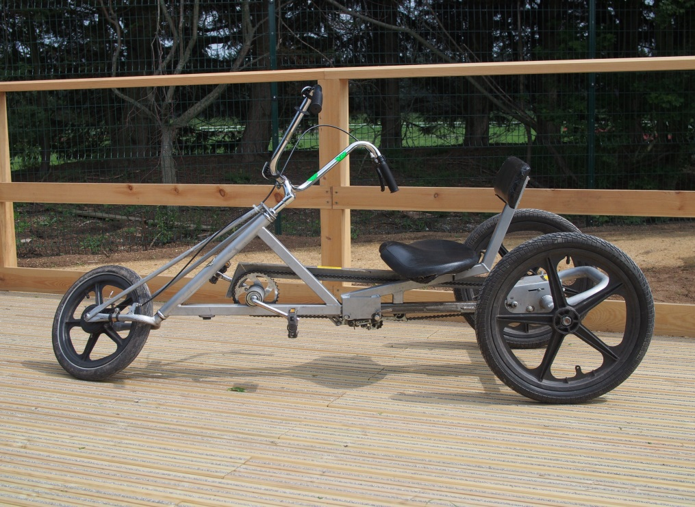 A silver adult size recumbent cycle on a wooden platform