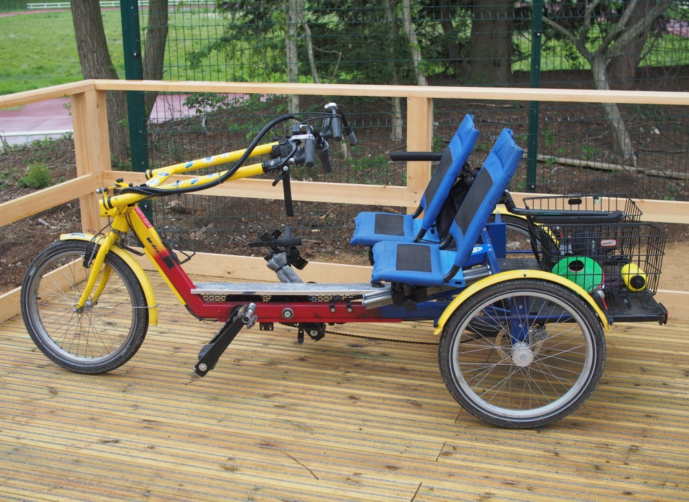 A yellow and red adult size side-by-side tandem on a wooden platform