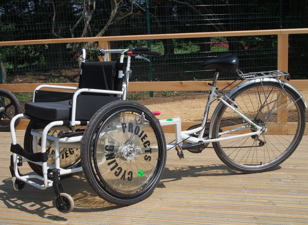 A white adult size wheelchair cycle on a wooden platform
