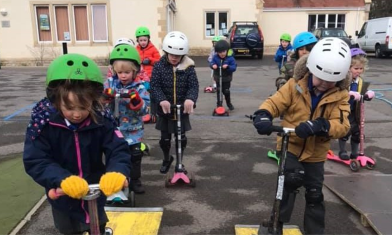 Photo of young children riding scooters in a playground