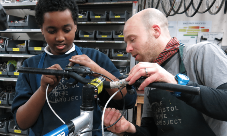 Photo of boy being shown how to fix a bike